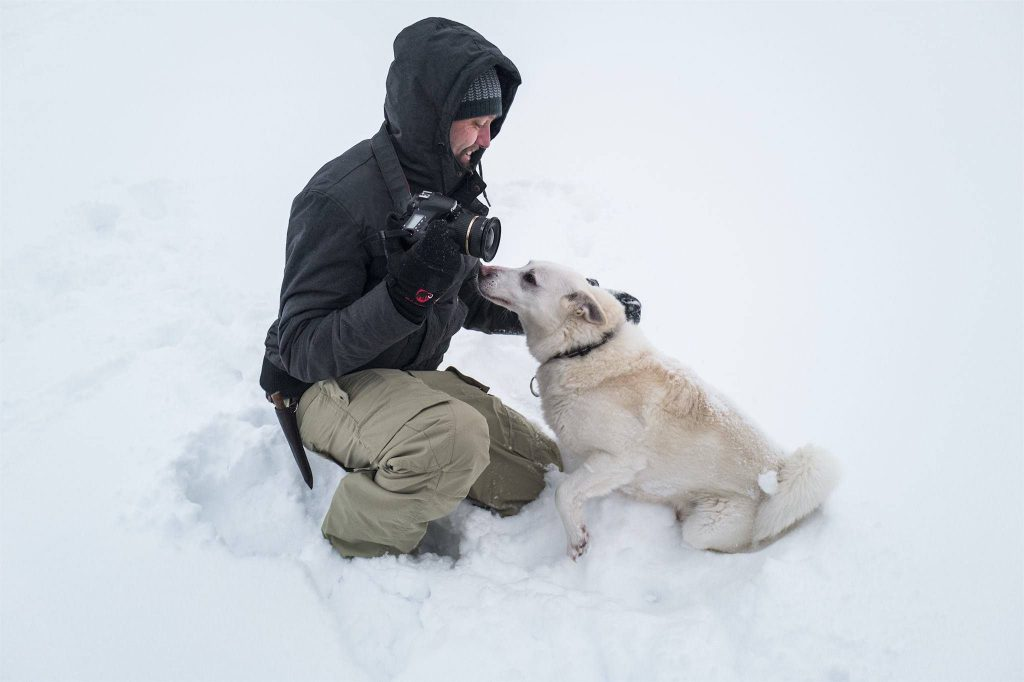 Matthias Huber in snow with dog